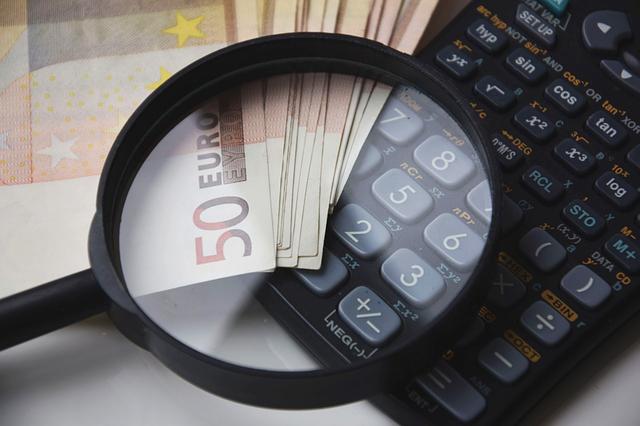 kalkulator, pieniądze i lupa