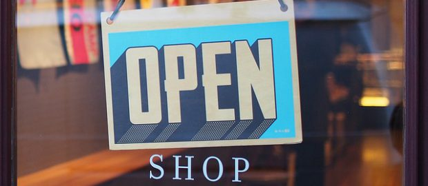 Drzwi wejściowe sklepu z tabliczką otwarte