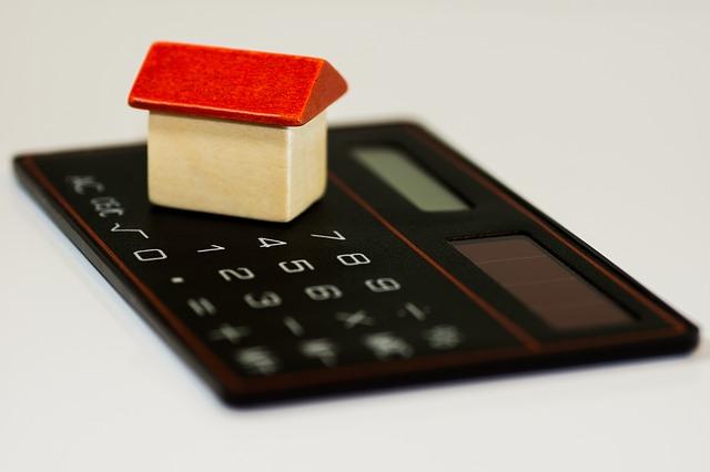 Drewniany domek stojący na kalkulatorze