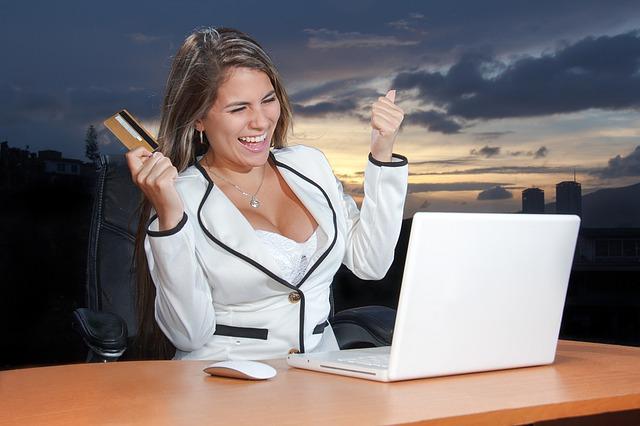 Kobieta siedzi przy laptopie z kartą kredytową