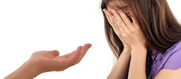 Załamana kobieta i wyciągnięta dłoń