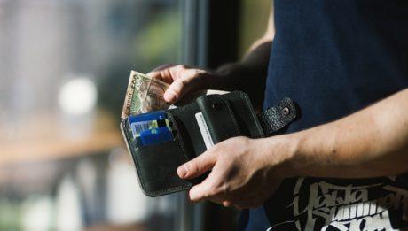 Człowiek trzymający portfel i pieniądze