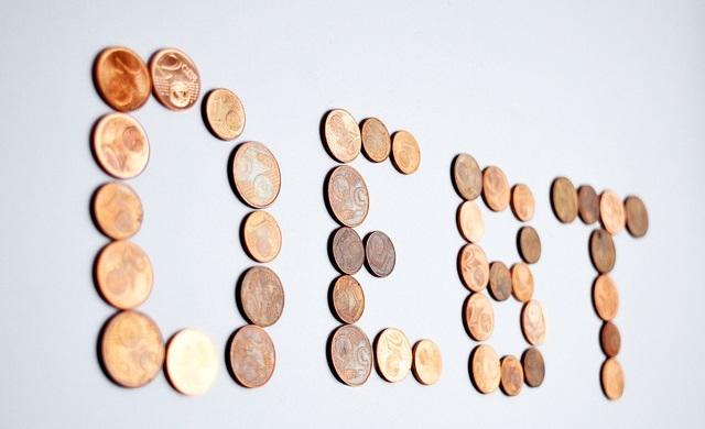 Monety ułożone w słowo debet
