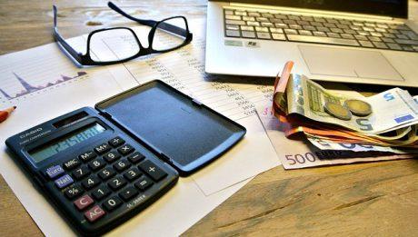 okulary, kalkulator, pieniądze i komputer na biurku