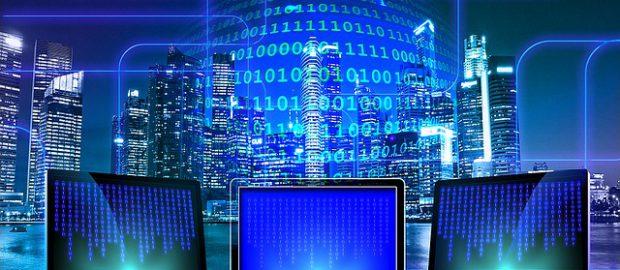 Trzy komputery i miasto w tle