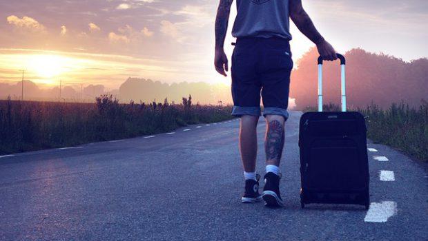 Chłopak z walizką na drodze