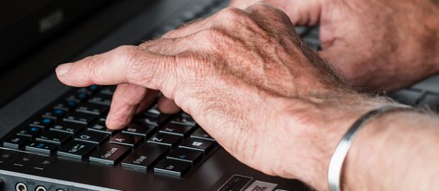 Senior piszący na komputerze