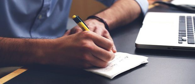 człowiek robiący notatki