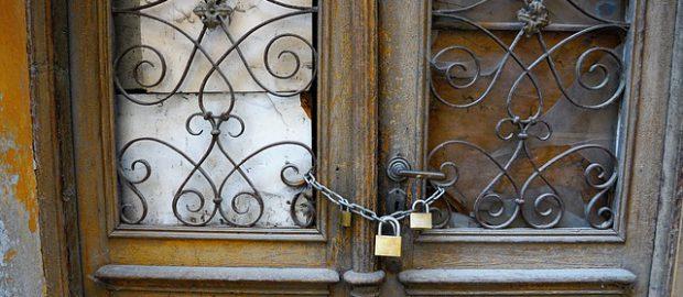 drzwi zamknięte łańcuchem z dwoma kłódkami