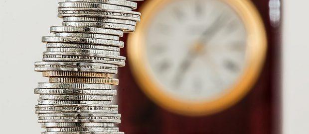 słupek monet na tle zegara