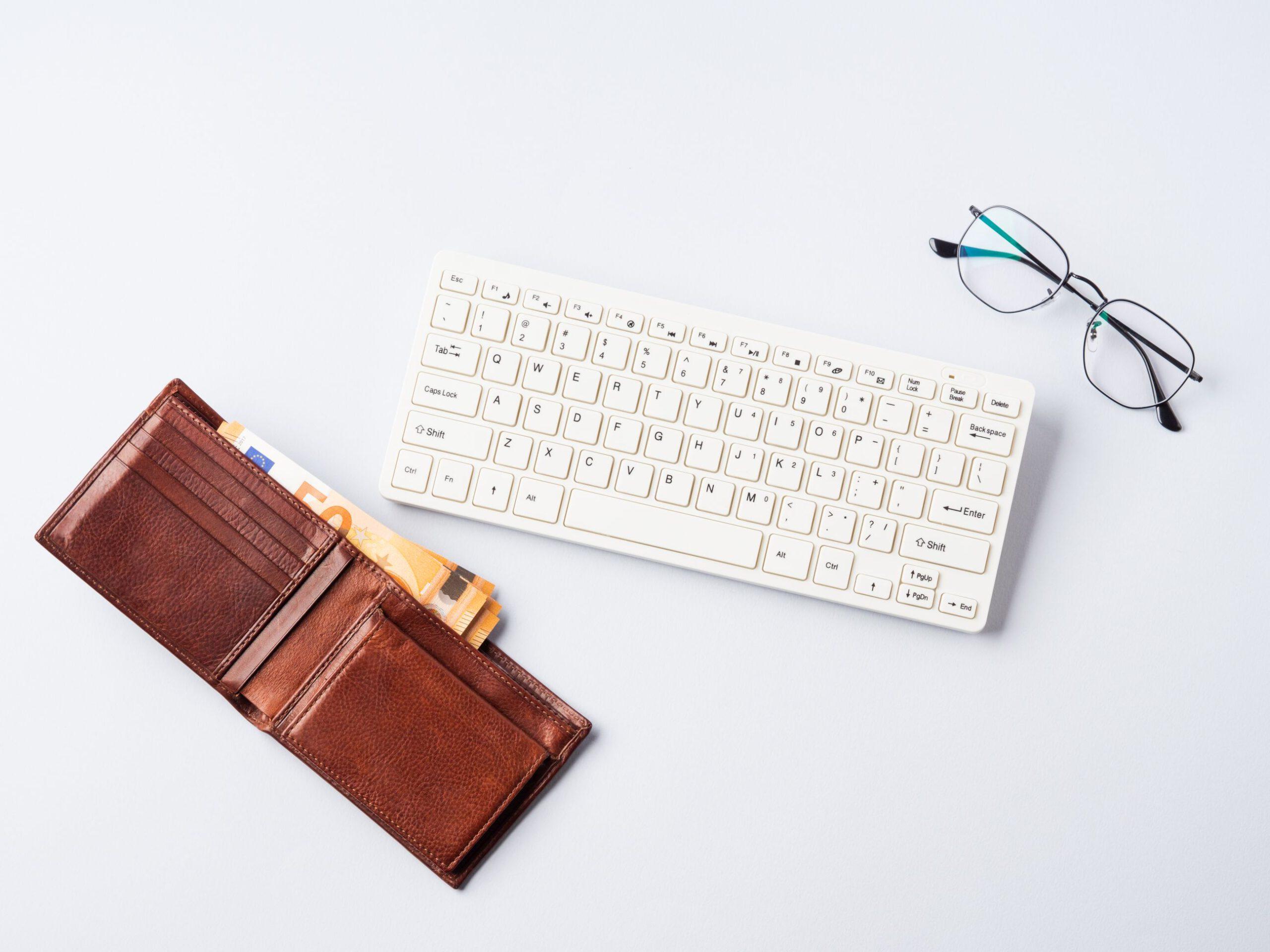 portfel z banknotami w środku obok klawiatury